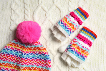 Warm hat and mittens on white knitted fabric, flat lay