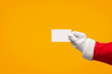 Santa Claus hand holding plastic credit card over isolated background.