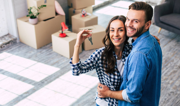 Happy housewarming. A young couple holds happily a key to their new home which they were so excited about, and this can't but make them feel overwhelmed with positive emotions.