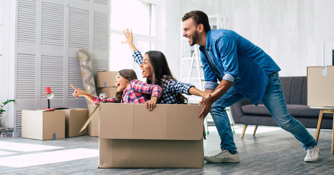 Little girl is riding in a cardboard box and pointing straight ahead while her mother imitates a plane and laughs, and father is pushing the box, enjoying their time together in their new house.
