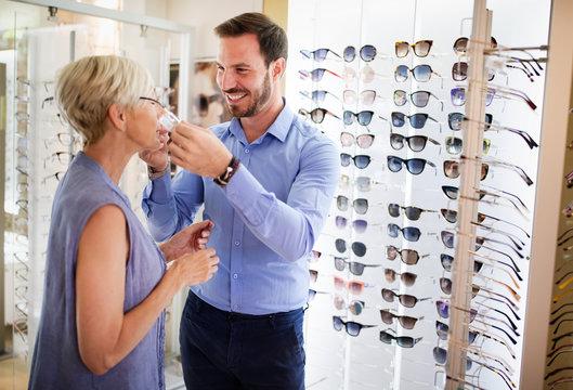 Pretty mature woman is choosing new glasses at optics store
