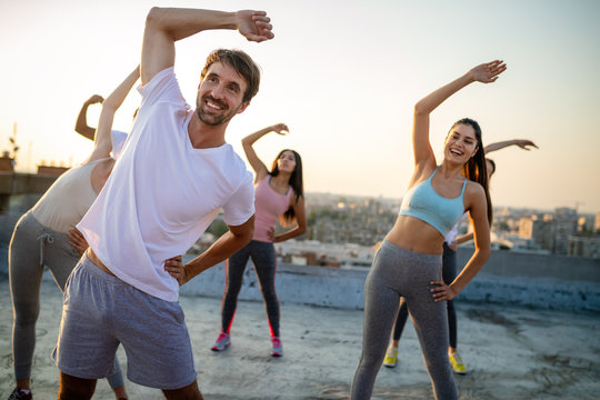 Group of friends fitness training together outdoors living active healthy