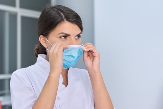 Portrait of young woman doctor nurse in protective medical face mask