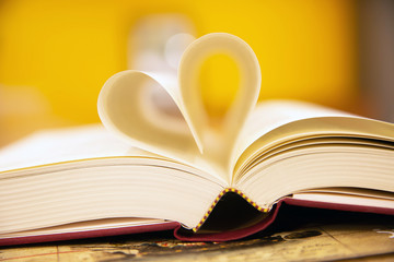 Close up a book image in heart shape on the table at library room concept of lifestyle love to read.