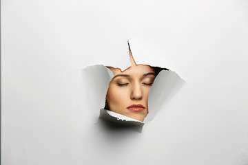 Woman looking out from a hole of torn paper