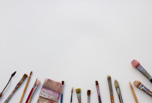 some painting brushes on the bottom of a white paper 白い画用紙とその下に並んだ絵筆