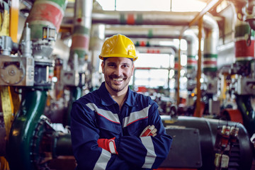 Smiling caucasian energy plant worker dressed in working clothes and with helmet on head standing...