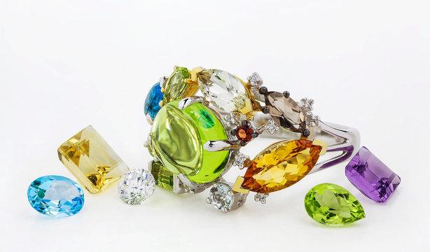 Golden ring. Golden ring with citrine, diamond; garnet, sapphire, chrysolite, amethyst, smoky quartz, emerald, topaz on white background.