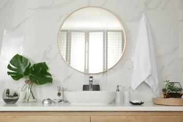 Stylish bathroom interior with vessel sink and round mirror