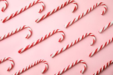 Flat lay composition with candy canes on pink background
