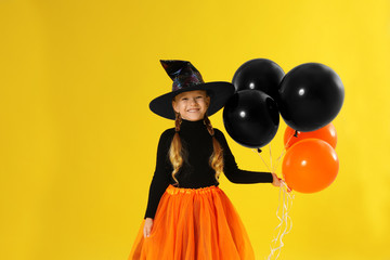 Cute little girl with balloons wearing Halloween costume on yellow background
