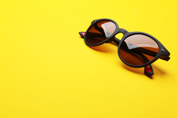 Stylish sunglasses on yellow background, space for text. Fashionable accessory