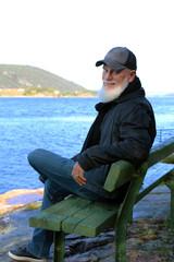 bearded man on a bench near the ocean
