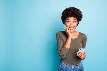 Fototapete - Portrait of scared emotions expression mulatto girl use cellphone have social media trouble failure send sms by mistake panic nail bite look wear green trendy pullover isolated blue color background