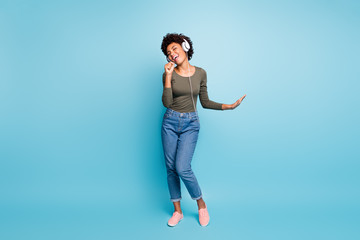 Full length body size photo of excited cheerful fun positive cute girlfriend singing into imaginary microphone wearing jeans denim green sweater dancing isolated over vivid blue color background