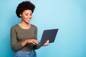 Photo of cheerful creative cute nice freelance worker wearing jeans denim holding electronic device with her hands laptop working with technology isolated over vivid color blue background