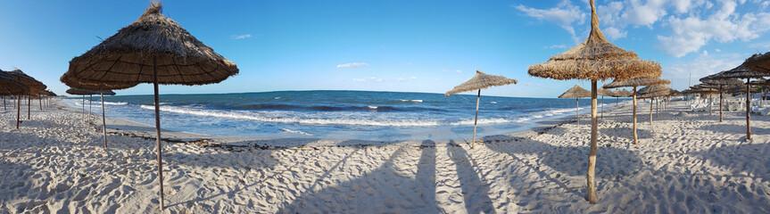 Empty sandy sea beach with many umbrellas, footprints and shadows