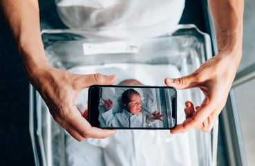 Mother taking picture of her newborn baby with smart phone