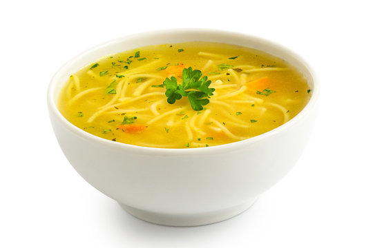 Instant chicken noodle soup in a white ceramic bowl isolated on white. Parsley garnish.