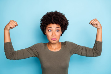 Fototapete - Portrait of confused negative afro american girl show her muscles dont understand why she weak after workouts wear casual style outfit isolated over blue color background