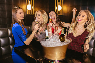 Happy women clinking champagne glasses and celebrating at night club