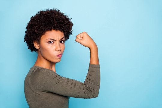 Photo of black millennial girl showing you her biceps thinking on result boasting about her strength isolated over vivid color background