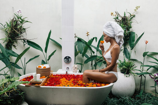 Woman relaxing in outdoor bath with flowers in Bali spa hotel.