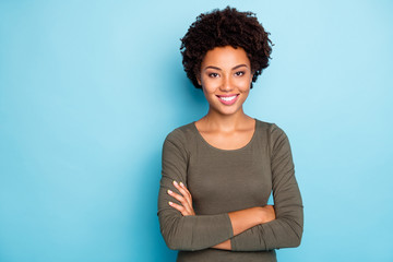Portrait of cheerful dreamy afro american girl cross her hands look reliable worker partner true leader wear casual style clothes isolated over blue color background