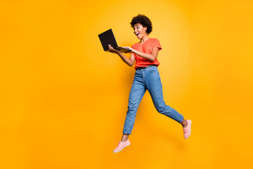 Full length photo of excited funny funky curly hair girl use her laptop find news information about sales jump wear denim jeans stylish trendy sneakers t-shirt isolated over yellow color background