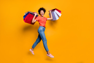 50 off. Full body photo of funky funny amazed wavy curly brown hair lady jump go walk hold bags from travel weekends wear trendy red t-shirt denim jeans isolated yellow color background Wall mural