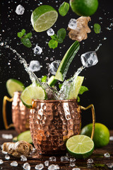 Famous splashing Moscow mule alcoholic cocktail in copper mugs, freeze motion effect.
