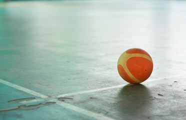Old basketball ball on the field floor