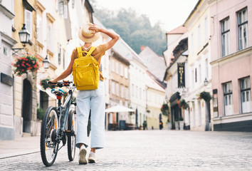 Girl with backpack and bicycle explores Ljubljana. Travel Slovenia