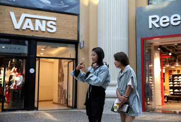Young women are seen outside a Vans store at a shopping center in Beijing
