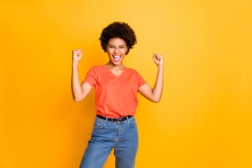 Photo of casual curly wavy trendy victorious excited overjoyed girlfriend crazy with victory wearing orange t-shirt jeans denim making fists isolated over yellow vivid color background