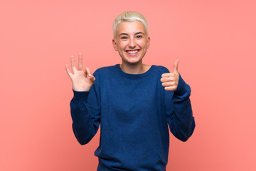 Teenager girl with white short hair over pink wall showing ok sign and thumb up gesture
