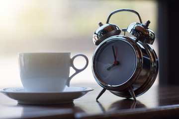 Coffee cup with alarm clock and sunshine in the morning.
