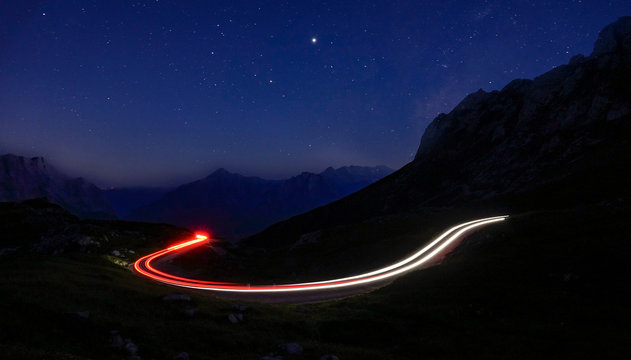 TIMELAPSE: Car lights create a blurry trail leading through mountains at night