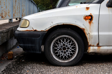 Rusty white Czech Skoda Felicia car damaged due to neglected care