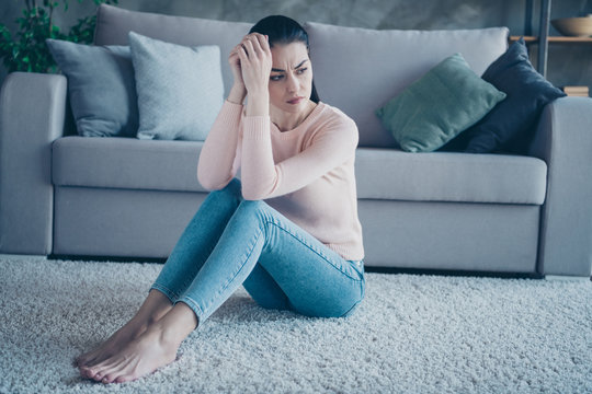 Photo of pretty lady suffering loneliness sitting floor on fluffy carpet near couch minded wearing pullover and jeans in apartment