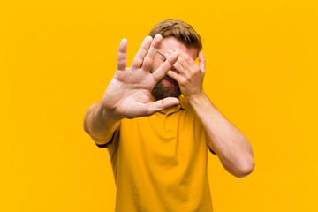 young blonde man covering face with hand and putting other hand up front to stop camera, refusing photos or pictures against orange wall