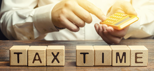 Wooden blocks with the word Tax time and taxpayer with a calculator. The concept of paying the tax rate. Taxation / burden. Pay off debts. Property / income annual taxes.