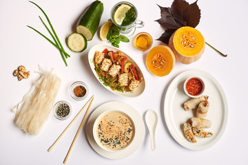 Flat lay of oriental dinner from soup with seeds, tempura shrimps and noodles with vegetables preparing for client. Three dishes lunch with mint tea ready for eating on white tablecloth.