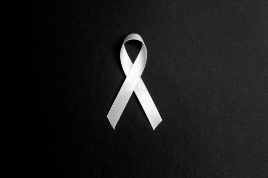 Lung cancer awareness ribbon on black background. November lung cancer awareness month.