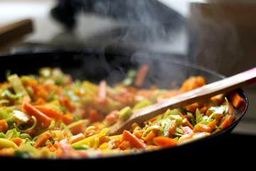 Cooking carrot, pumpkin, zucchini nad leek in wok. Selective focus, close-up.