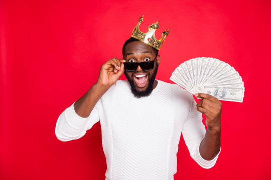 Portrait of shocked crazy dark skin man brown hair bearded hold fan of money scream wow win cashback x-mas lottery in million dollars wear gold tiara white jumper isolated over red color background