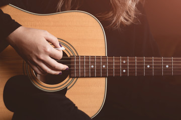 girl plays an acoustic guitar. close-up of strings