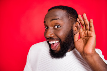 Close up photo of interested curious dark skin man hold hand near ears listen confidential promo about x-mas wonder feel impressed wear style white sweater isolated over red color background