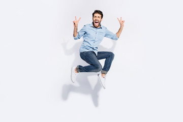 Full length photo of wild multiethnic guy jumping high yelling loud showing v-sign symbols wear casual denim clothes isolated white color background