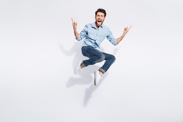 Full length photo of wild indian guy jumping high at hard rock concert making finger horns symbol wear casual denim clothes isolated white color background